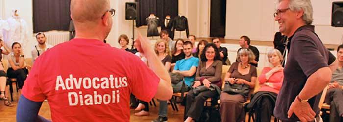 Christhard Landgraf (zappo - Agentur für Kommunikation, Berlin) schoss dann gänzlich übers Ziel hinaus. Mit einem T-Shirt kostümiert, welches die Aufschrift »Advocatus Diaboli« trug, formulierte er seine erste schroffe Frage: »Ich frage sie Herr Friedrich, sind sie ein Lügner?. In seinem Bulletin »Offener Brief zum Ateliergespräch« legte er noch einmal nach: »Ich habe keine Ahnung was Sie dazu getrieben hat, hier in Berlin zu versuchen, einen neuen Religionsstreit vom Zaun zu brechen (...)«.
