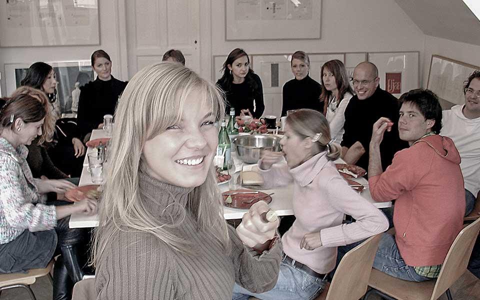 Studenten und Volontäre nach dem Ateliergespräch im Münchner Atelier von Wolfgang Beinert bei einem gemeinsamen Essen. Im Vordergrund Angela Brands. Am Tisch sitzend von rechts: Nicole Glur, Clovis Vallois, Cristoph Rankers, Bernhard Pompey, Lisa Roessler, Jasmin Lappe, Christina Bernd, Wolfgang Wick (verdeckt), Carmen Münkel, Jeong-Hee Hyung, Conny Altmann Sekulin (verdeckt) und Rosali Schnell.