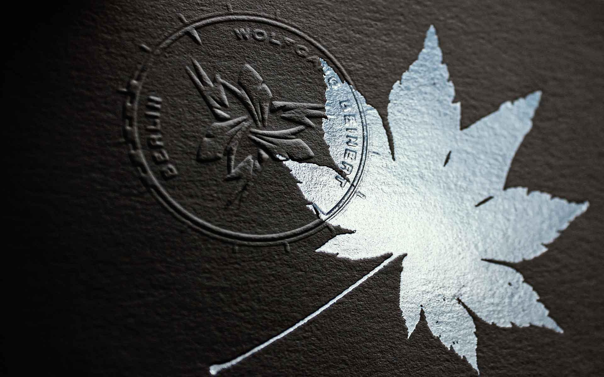 Druckveredelung, Blindprägung eines Logos auf texturierten Naturpapier mit Heißfolienprägung.