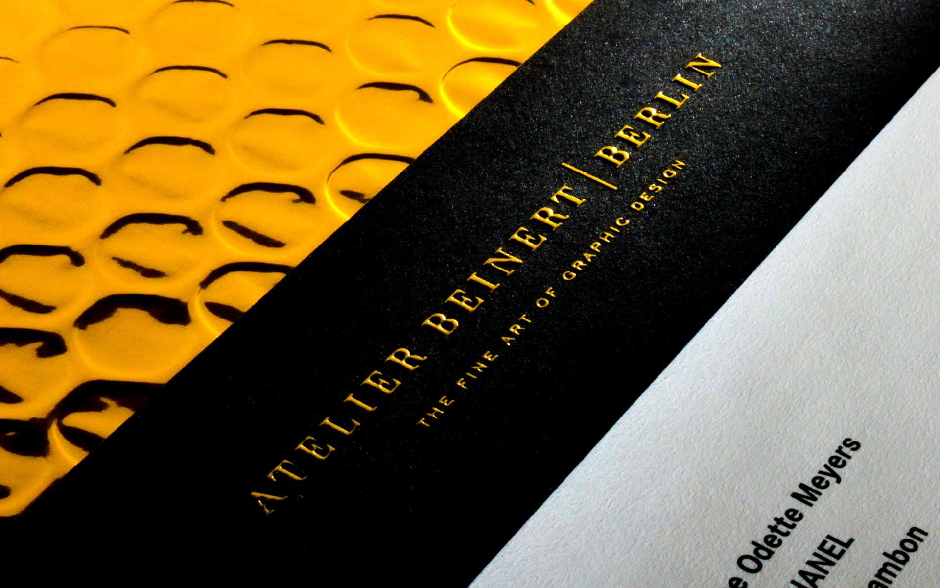 Druckveredelung, Blindprägung mit goldender Heißfolienprägung auf einer texturierten Etikette.